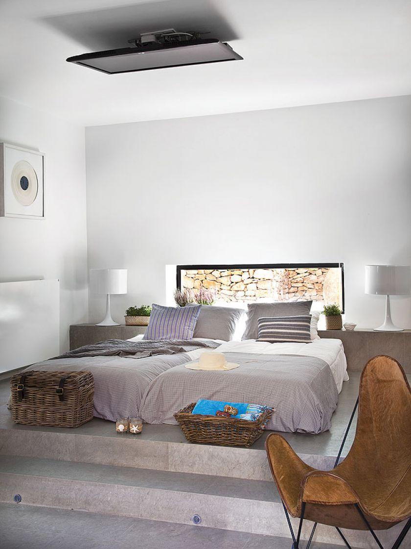 Sypialnia urządzona w szarościach, granacie i naturalnym kolorze drewna i skóry.
