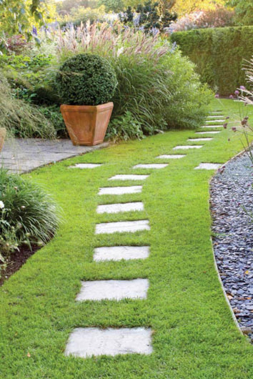 Szare betonowe płyty w trawniku dobrze grają z kora wysypana na rabatach. GAP PHOTOS/MEDIUM