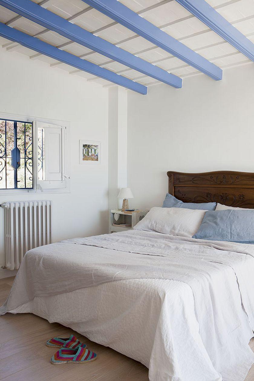 Sypialnia z błękitnymi drewnianymi belkami pod sufitem.
