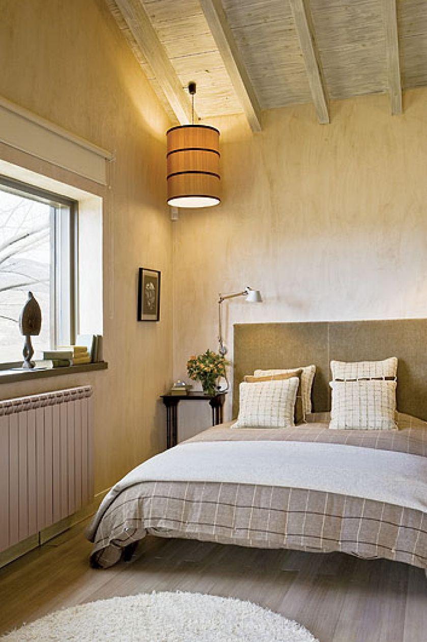 Zabawa światłem. Na suficie żyrandol z drukowanego jedwabiu. Przy wezgłowiu łóżka aluminiowe lampki.