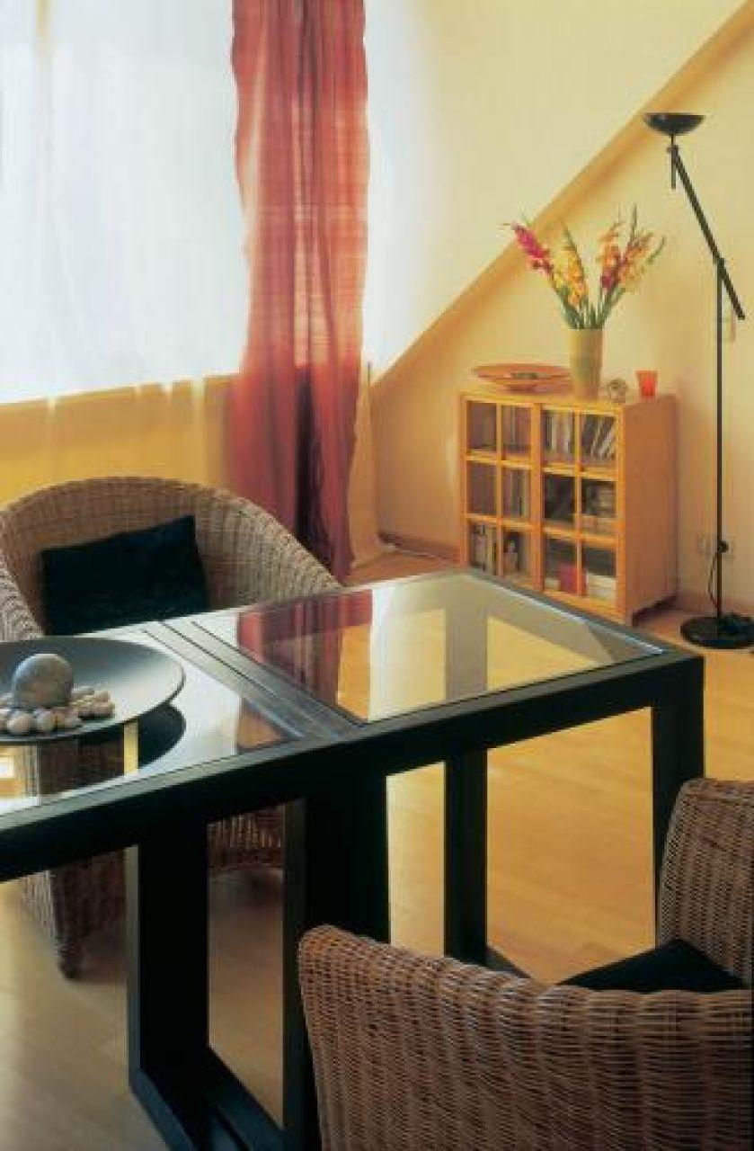 Plecione fotele, stół ze szklanym blatem i niska biblioteczka,