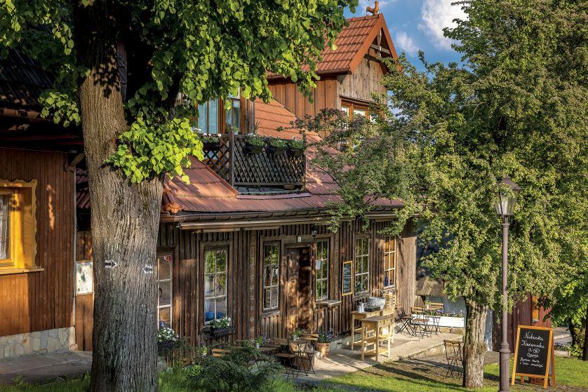 Niskie drewniane domy z charakterystycznie ściętym i dachami otaczają pochyły rynek. To dzięki nim w