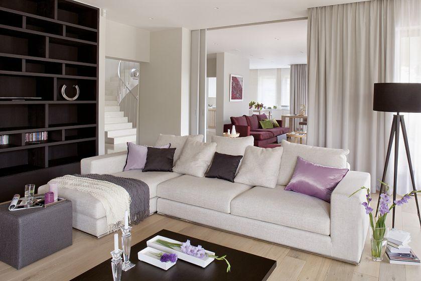 Duży salon można przedzielić drzwiami obitymi tkaniną. Obie kanapy właściciele kupili w Casa Marvell. Stół i stolik kawowy -