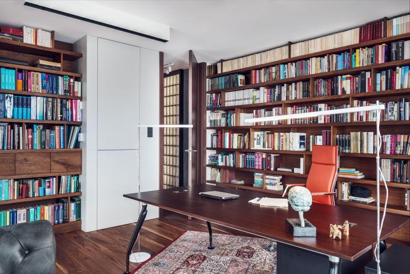Klasycznego charakteru nadają ciężkie, czarne żaluzje, sofa w stylu chesterfield oraz klasyczny perski dywan.