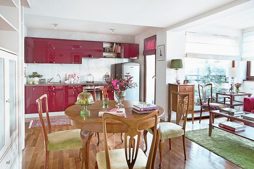 Kolorowe nowoczesne meble w kuchni współgrają z naturalnym drewnem starego stołu.