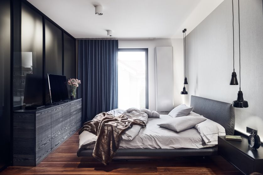 Lekko mroczna sypialnia z dużym łóżkiem. Dominują w niej szarości i miękkie materiały. Kontrastem jest