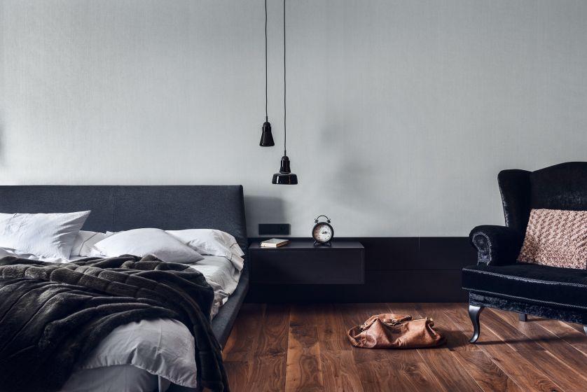 Sypialnia urządzona jest minimalistycznie. Nowoczesny charakter podkreślają wiszące na długich kablach lampy, spełniające