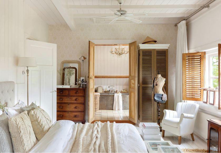 Duża jasna sypialnia powstała z połączenia dwóch pokoi. Komoda, fotel i manekin to antyki.