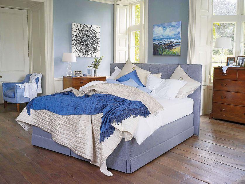 Łóżko Servant (14 100 zł) obite błękitną tkaniną z dopasowaną kolorystycznie pościelą.
